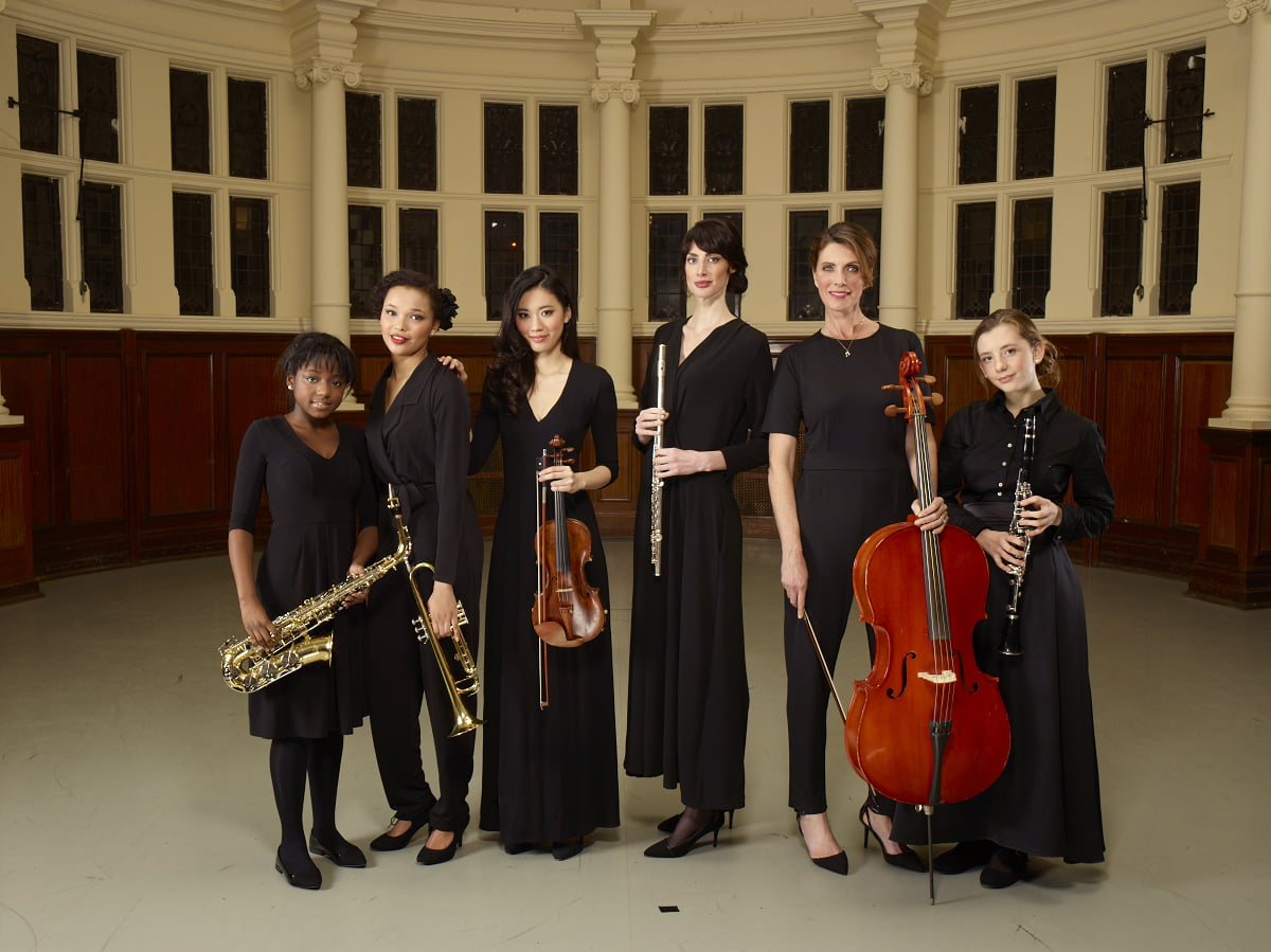 Group of young classical musicians - cello, violin, saxophone, clarinet, flute, trumpet